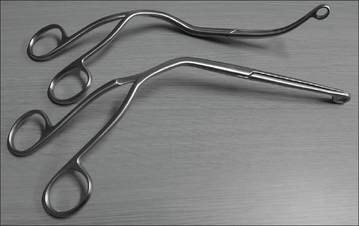 Figure 1: Magill and Suzy forceps. Conventional Magill forceps (near side) and Suzy forceps (far side). Note that the middle to distal portion of the Suzy forceps is curved to fit anatomically designed curved blade of McGrath MACTM video laryngoscopes